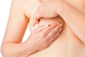 Medicine and disease - mature woman examine her breast to prevent breast cancer